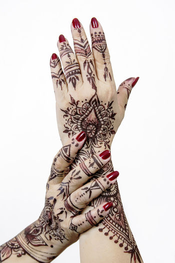 Close-Up Of Woman Hand With Henna Tattoo Over White Background