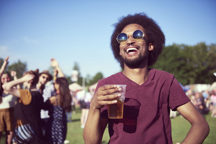 Young man drinking water from sunglasses against sky
