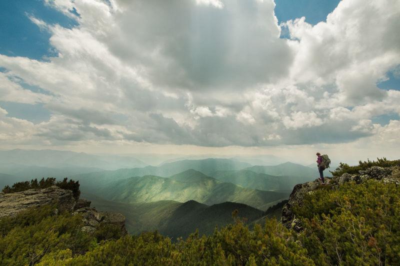 Full Length Of Hiker Standing On Mountain Peak Against Sky