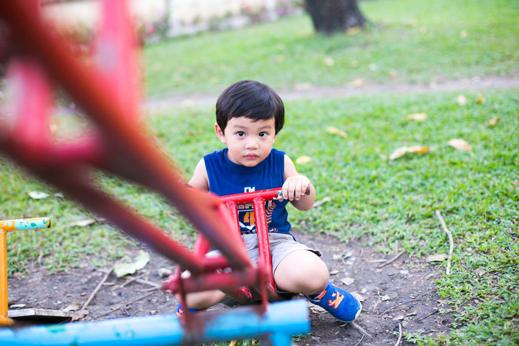 Portrait of cute baby boy sitting on seesaw