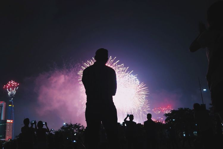 Rear View Of Silhouette People Looking At Firework Display In Sky At Night