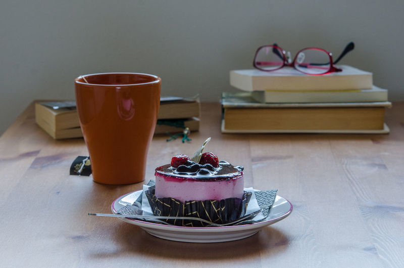 High Angle View Of Blueberry Cheesecake And Coffee Served On Table