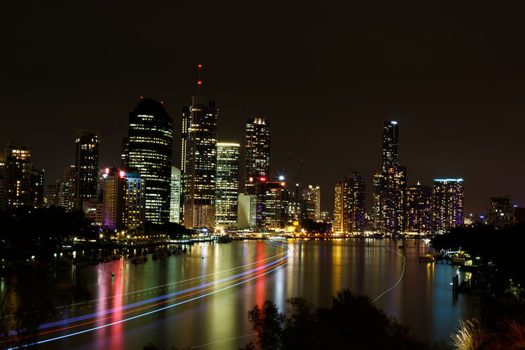 High Angle View Of Light Trails On Brisbane River Against Modern Buildings