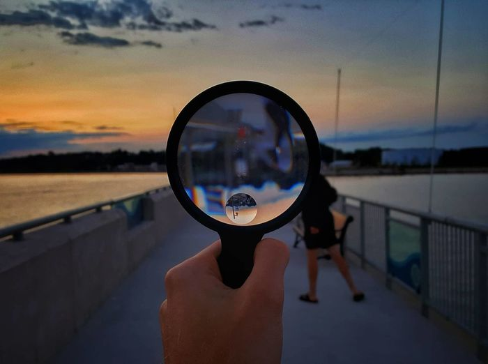 Close-Up Of Hand Holding Magnifying Glass Against Sky