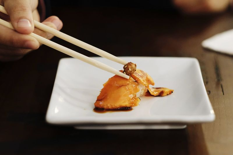 Hand of a man using chopsticks to hold a piece of nigiri sushi.