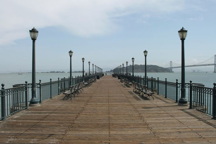 Row of benches and gas lights on pier against sky