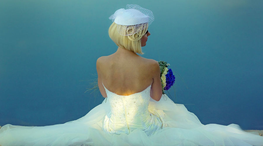 Rear View Of Bride Standing Against Blue Background
