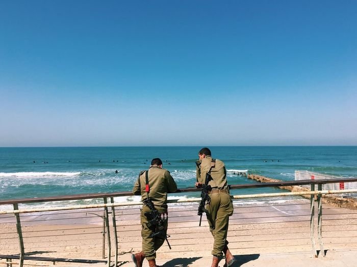 Rear View Of Security Guards With Guns Standing By Railing At Beach