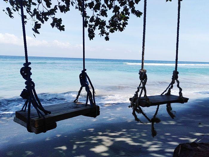 View of swing in sea against sky