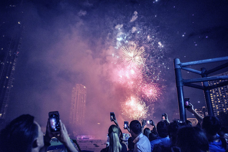 Crowd photographing firework display through mobile phone at night