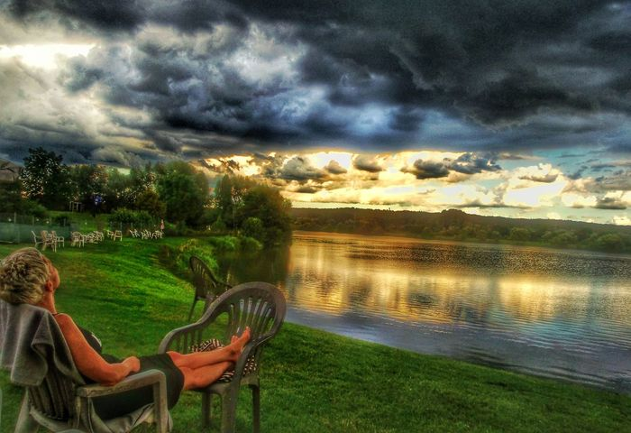 Sun Behind Clouds Lakeside Woman Relaxing In The Foreground Dramatic Sky Clouds And Sky Before Sunset A Storm Is A Brewing Reflections In The Water Reflections And Shadows Calm Before The Storm Langenselbold Germany🇩🇪 Showcase July Hidden Gems  Colour Of Life Been There.