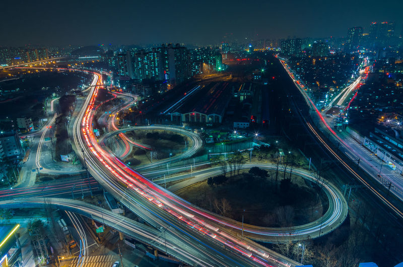 Aerial view of elevated roads in illuminated cityscape at night