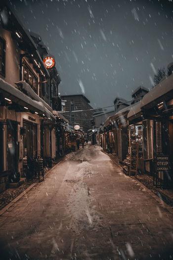 Illuminated street amidst buildings against sky during rainy season
