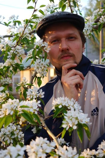 Portrait of young man against white flowering plants