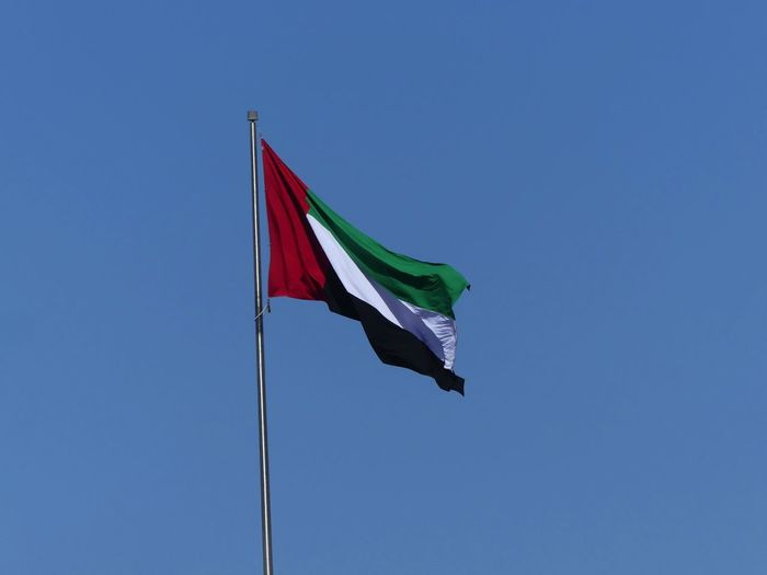 United Arab Emirates Flag 2019 Dubai UAE 2019 Flag Low Angle View Patriotism Blue Sky Wind Clear Sky No People Symbolism Waving Pole Striped National Icon Unfurled Flag Sunlight Red Green White Andblack Colour UAE Flag Composition Outdoor Photography