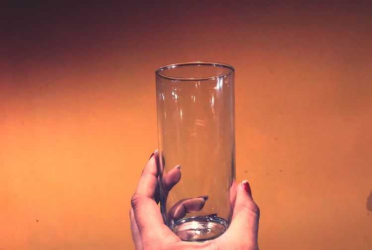 Cropped hand of woman holding drinking glass against wall