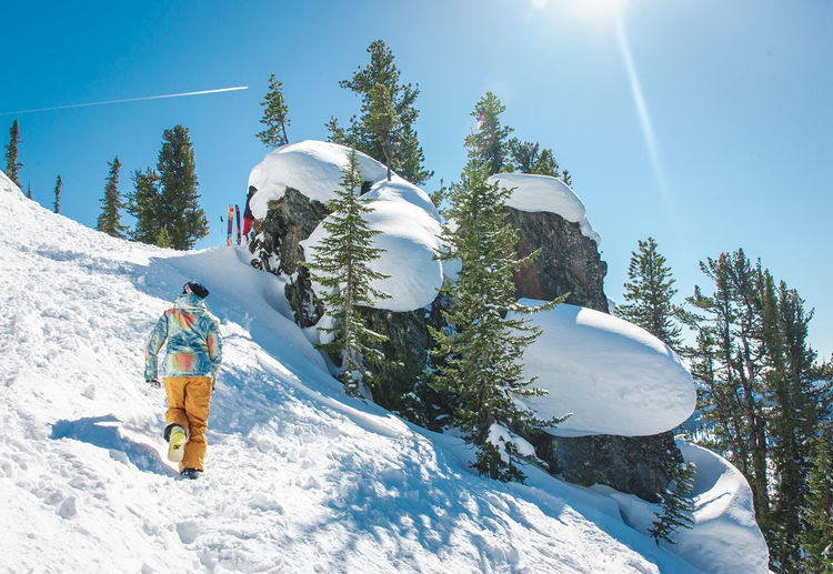 Rear view of hiker climbing on snow covered rocky mountain against sky during sunny day
