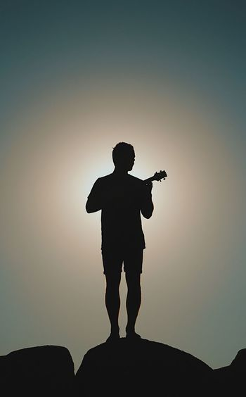 Silhouette mid adult man playing guitar while standing on rock formation against blue sky