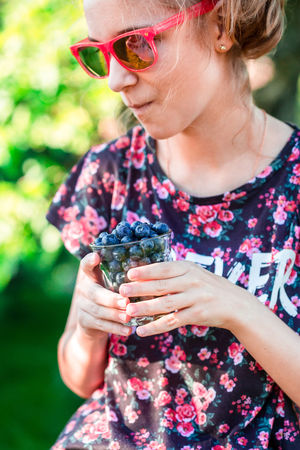 Happy girl enjoying eating the fresh blueberries outdoors. Teenager girl wearing flowery red-blue blouse and red sunglasses. Garden in the background. Vertical shot Berries Dessert Eating Freshness Life Woman Young Berry Blueberries Blueberry Enjoying Enjoyment Female Food Fresh Fruit Garden Girl Healthy Joy Organic Outdoors person Summer Sweet