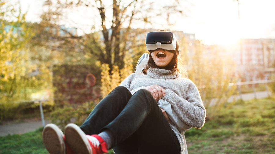 Couple of young adults playing with VR headsets Couple Friends Fun Grass Love Virtual Reality Friendship Headset Joy Leisure Activity Outdoors Park Real People Smile Summer Technology Virtual Reality Simulator Vr Warm Clothing