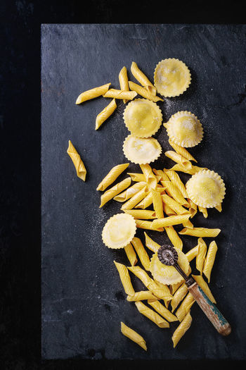 Homemade ravioli and garganelli pasta with flour and wooden roller over black slate background. Top view Black Background Flour Food Food Photography Garganelli Healthy Eating Homemade Food Italian Food Pasta Pasta Cutter Penne Preparation  Ravioli Sardi Raw Food Slate Space For Text Top View Of Food Uncooked Pasta Yellow