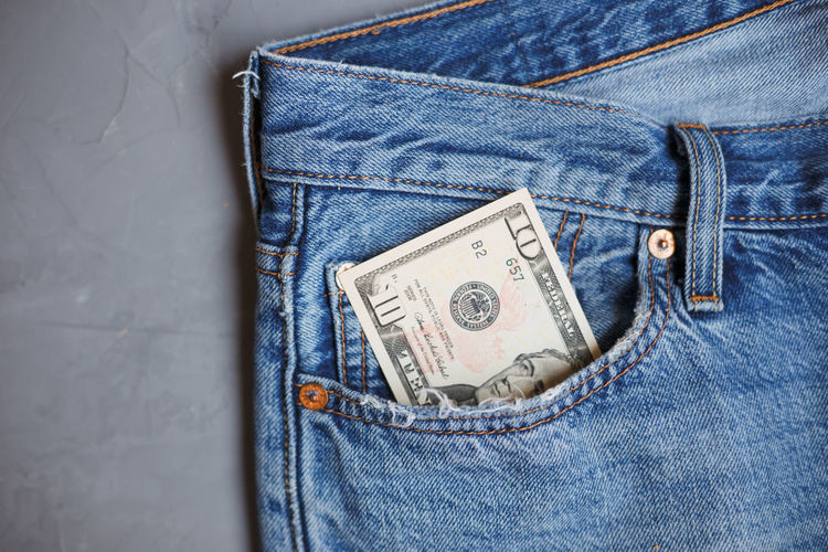 Money financial banknotes in a pocket of blue jeans on gray background.