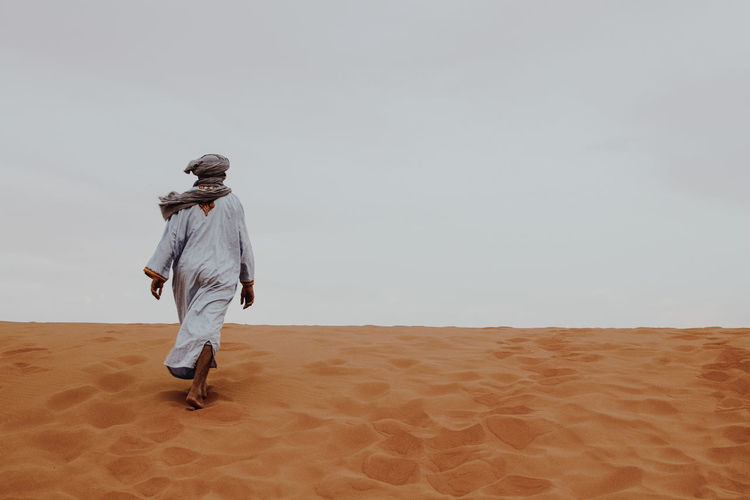 Rear View Of Man Walking On Sand Dune Against Clear Sky