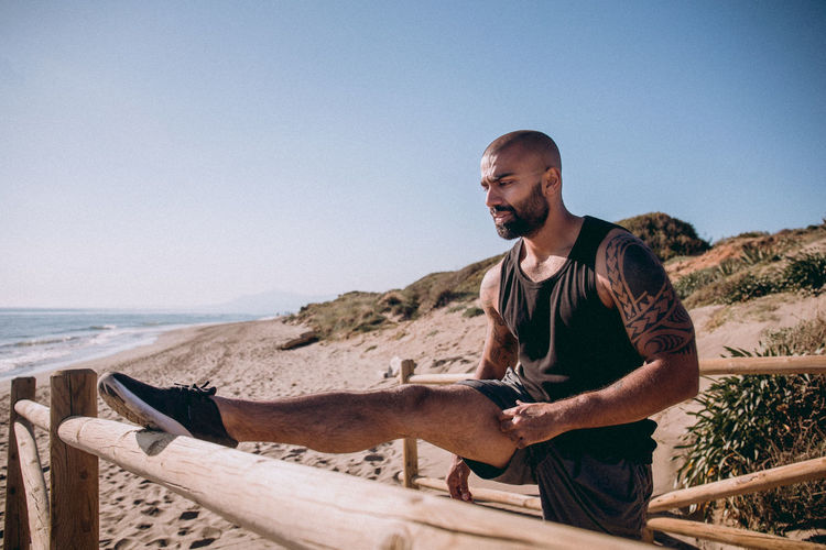 Man stretching on wooden railing at beach against sky