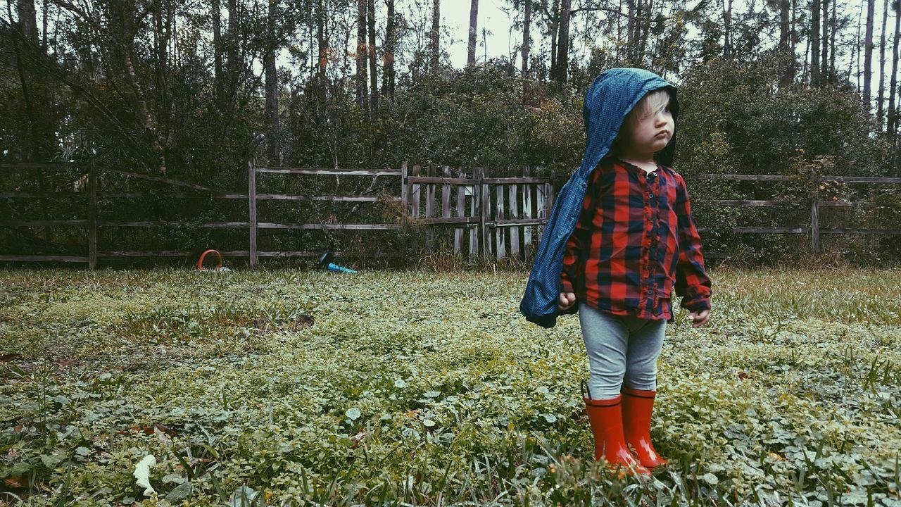 Child Wearing Raincoat Standing On Field During Rainy Season