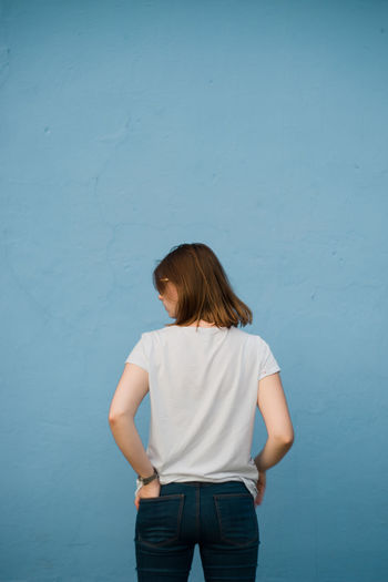 Rear view of young woman standing against blue wall