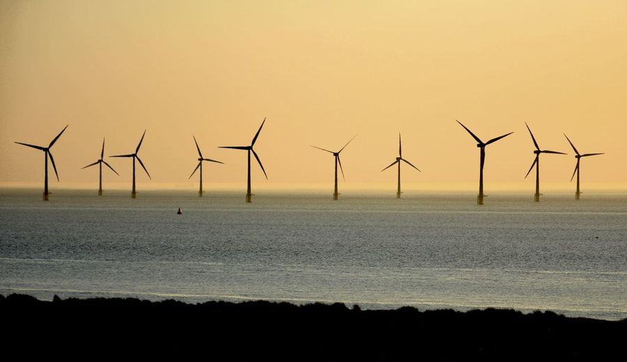 Wind turbines on beach against sky during sunset