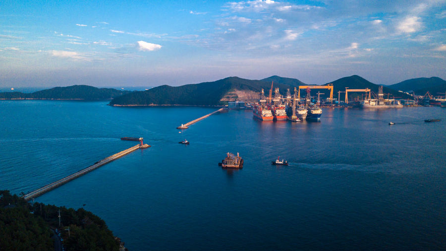 Aerial view of Daewoo shipyard in okpo city, South korea. Scenery consist of shipyard inside the bay, commercial ship, platform, heavy crane and building. Construction Container DSME Industrial Offshore South Korea Background Boat Building Commercial Drill Drilling Rig Equipment Floating Geoje Marine Offshore Platform Okpo Platform Sea Ship Shipbuilding Shipyard Shipyard Crane Water
