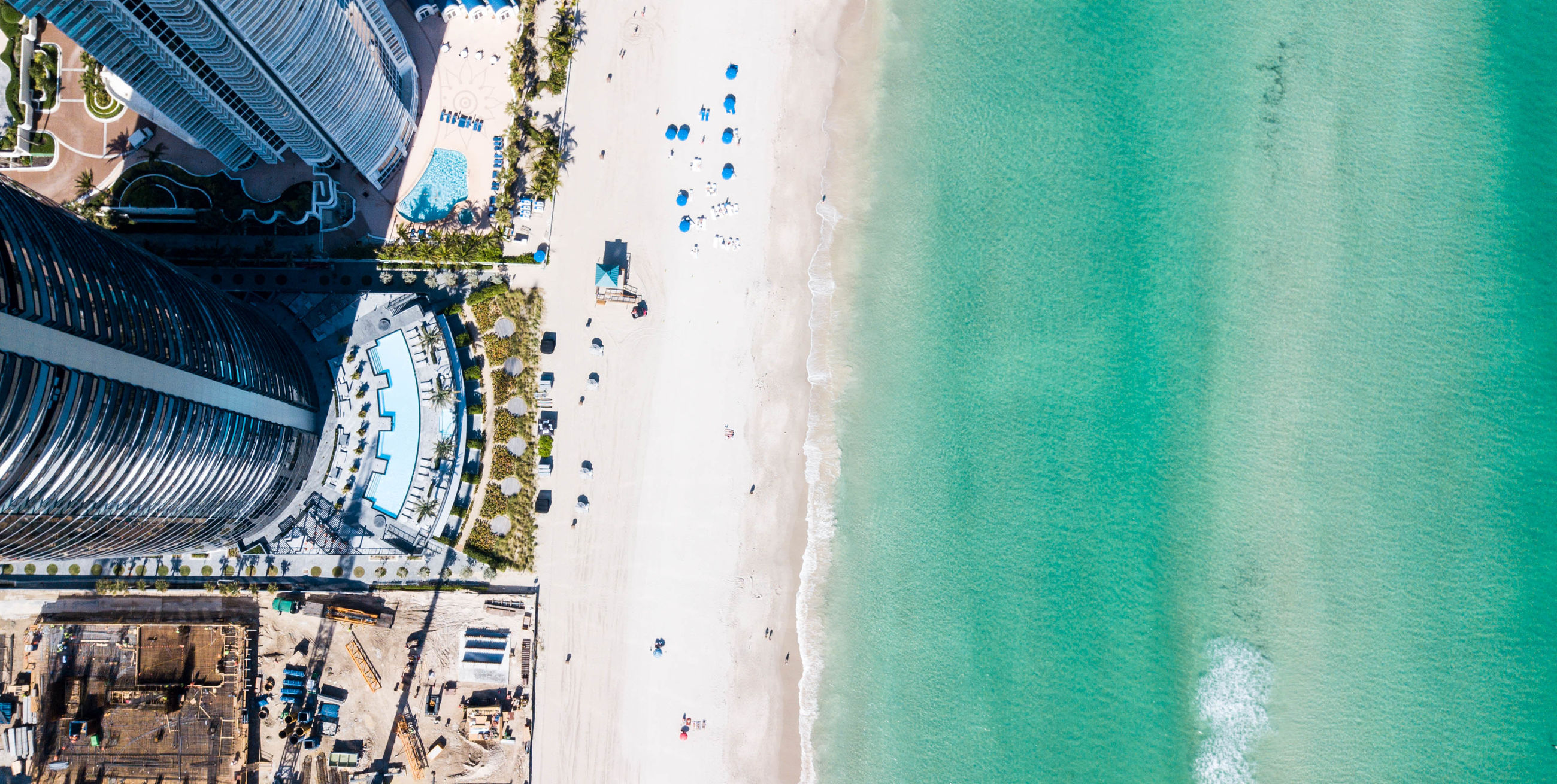 water, land, sea, day, nature, beach, architecture, built structure, incidental people, city, travel, outdoors, high angle view, building exterior, tourism, beauty in nature, real people, holiday, sand
