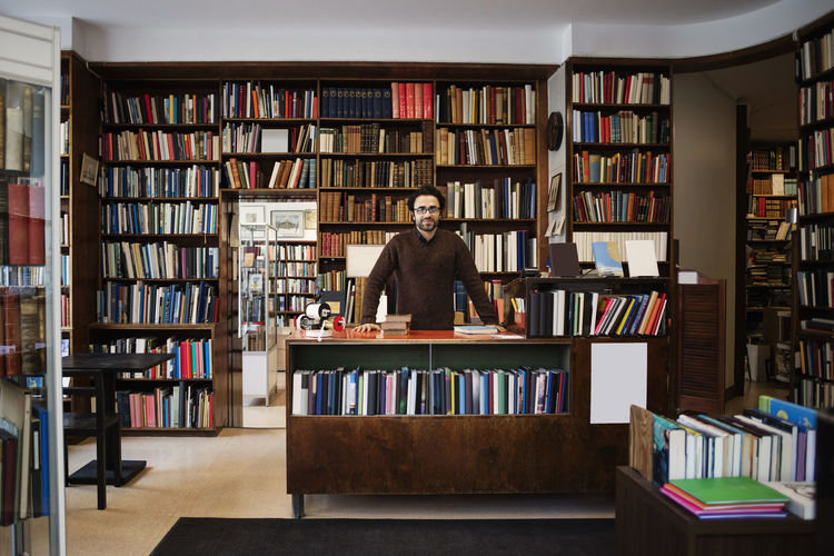 Man standing by books in library