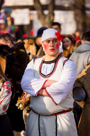 PERNIK, BULGARIA - JANUARY 26, 2018: Young man with painted cheeks in red and fake red carnation crosses his arms at the annual International Festival of Masquerade Games Surva in Pernik, Bulgaria ExpressYourself Facial Expressions Makeup Pernik Red Bulgaria Bulgarian Folklore Costume Day Expression Facial Expression Festival Focus On Foreground Large Group Of People Men Outdoors Real People Red Color Rouge Standing Surva Tradition Traditional Clothing White Young Adult