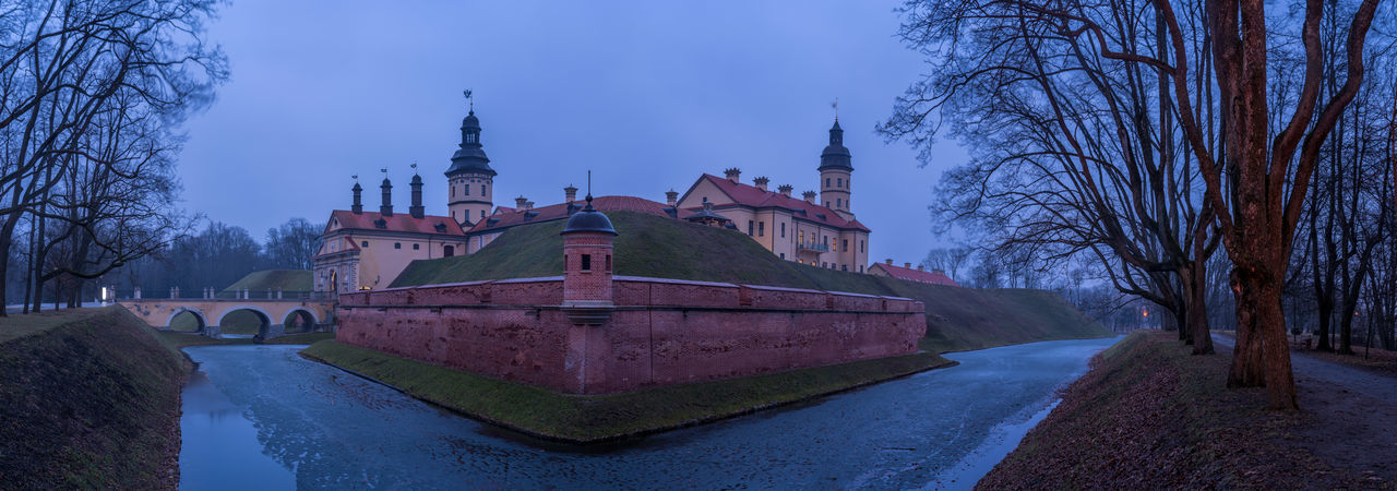 The Nesvizh Castle outside of Minsk Belarus captured during a moody foggy in high resolution panorama Architecture Belarus Blue Hour Brick Wall Castle Frozen Minsk Moody Sky Panorama Tree Wall Bridge Corner Dusk Fog History Moat Moated Castle Nesvizh Castle No People Sky Tower