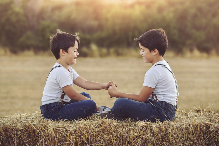 Friends Fun Funny Siblings Boys Brothers Child Childhood Family Friendship Grass Happiness Love Nature Playful Sitting Smiling Son Straw Twins