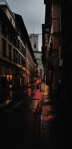 Wet street amidst buildings against sky in city