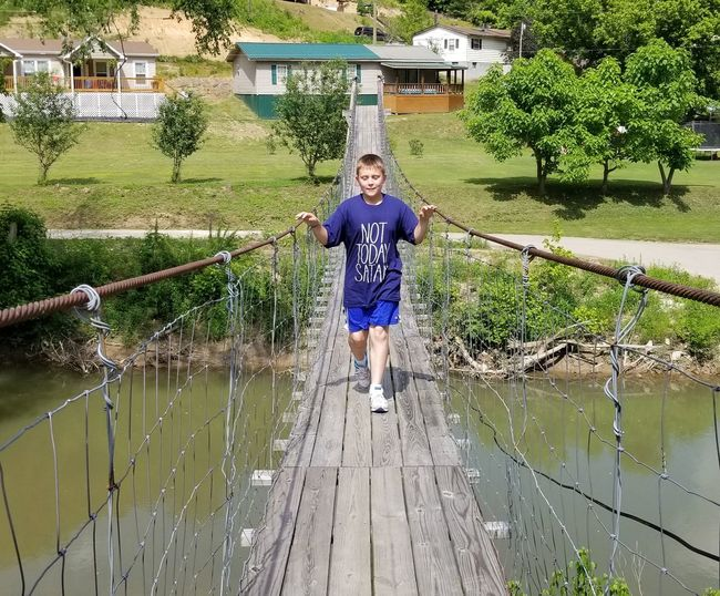 Cute boy walking on footbridge over lake