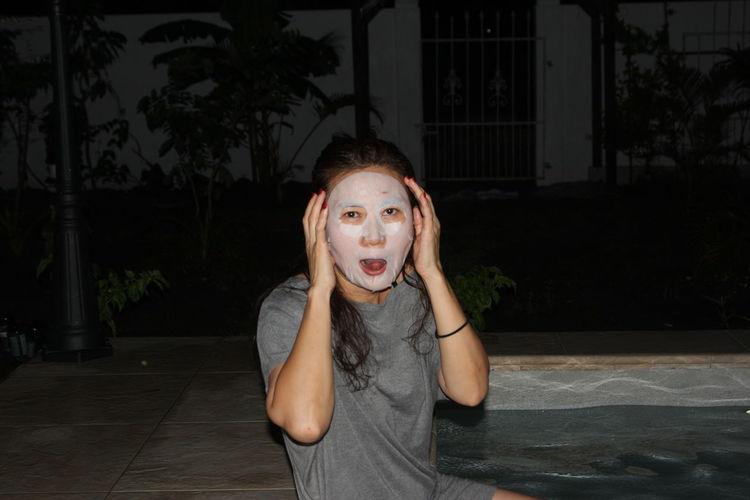 Portrait Of Woman Wearing Facial Mask At Night