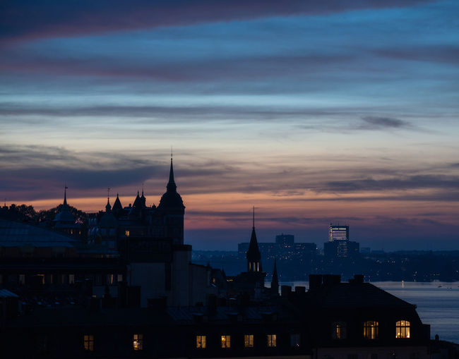 Architecture Built Structure Building Exterior Sky City Cloud - Sky Nature Sunset Outdoors Cityscape Slussen Building Travel Destinations No People Religion Belief Orange Color Tourism Travel Spire  Silhouette Building Silhouette Autumn Dusk Evening