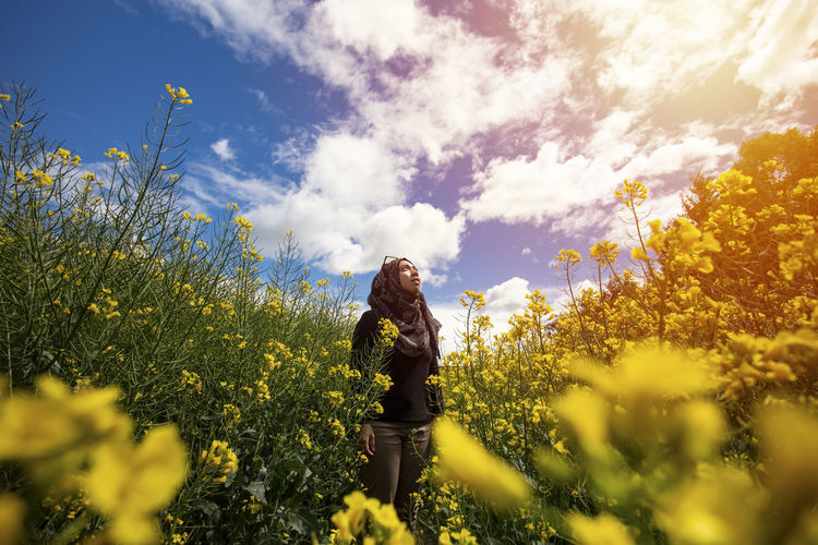 Young woman standing amidst yellow flowering plants against sky