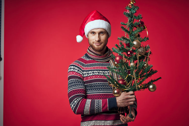 Portrait of woman with christmas tree against red background