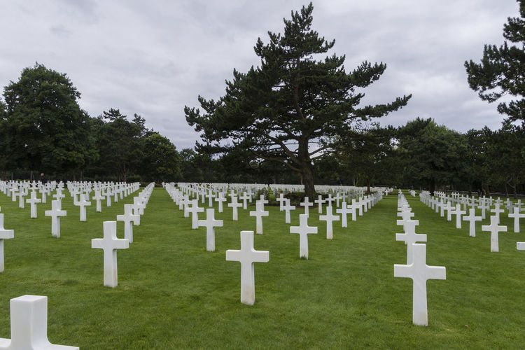 Colleville-sur-Mer (France). 07/24/2017. American War Cemetery next to Omaha Beach, where the Americans suffered the greatest losses during D-Day. 9,387 American soldiers were buried here, It is the most famous war cemetery in Normandy. Cross D-Day Patriotism Cemetery Cloud - Sky Cross Grass Grave Gravestone Graveyard In A Row Memorial Military Monument Omaha Beach Sadness Spirituality The Past Tombstone Tranquility Travel Destination War Cemetery