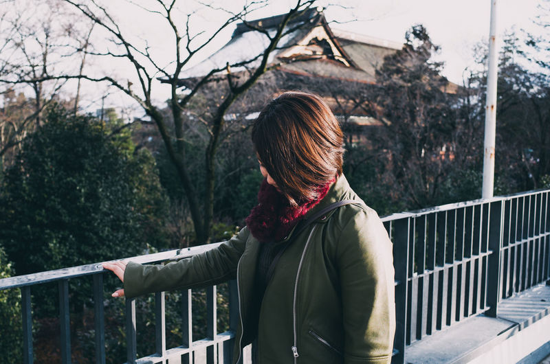 Rear view of woman standing by railing against trees during winter