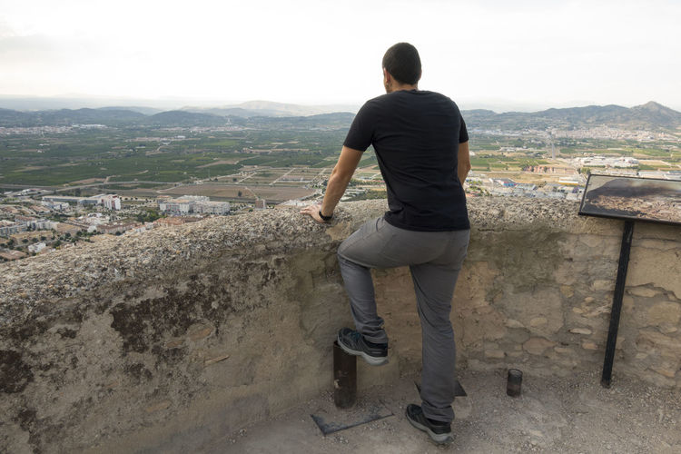Skyline Watching The Sunset Architecture Built Structure Casual Clothing Day Doing Environment Full Length Leisure Activity Lifestyles Looking At View Men Mountain Nature One Person Outdoors Real People Rear View Ruin Sky Standing Xativa Young Adult Young Men