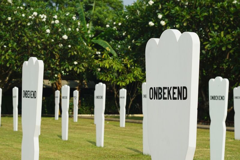Text on white cemetery against trees