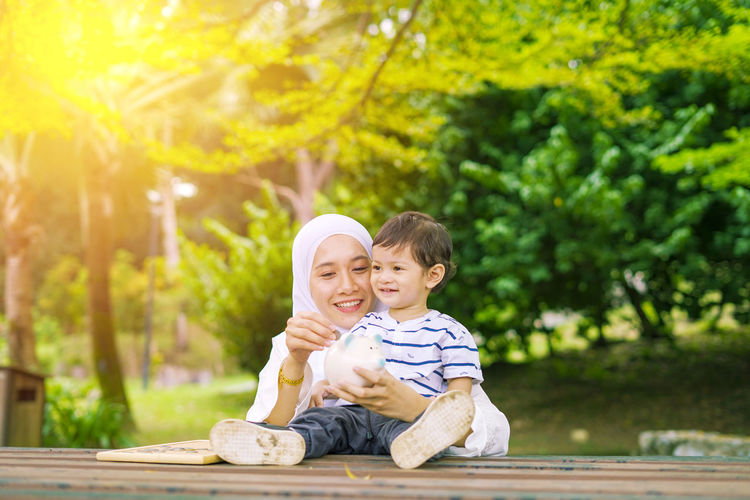 Young woman with her cute son learn how to put coins into piggy bank. Future planning concept. Child Childhood Togetherness Family Males  Men Bonding Son Innocence Two People Emotion Sitting Boys Smiling Day Offspring Happiness Casual Clothing People Tree Positive Emotion Outdoors Sister