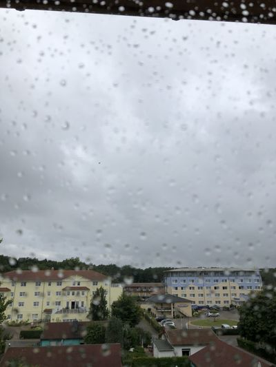 Buildings against sky seen through wet glass window