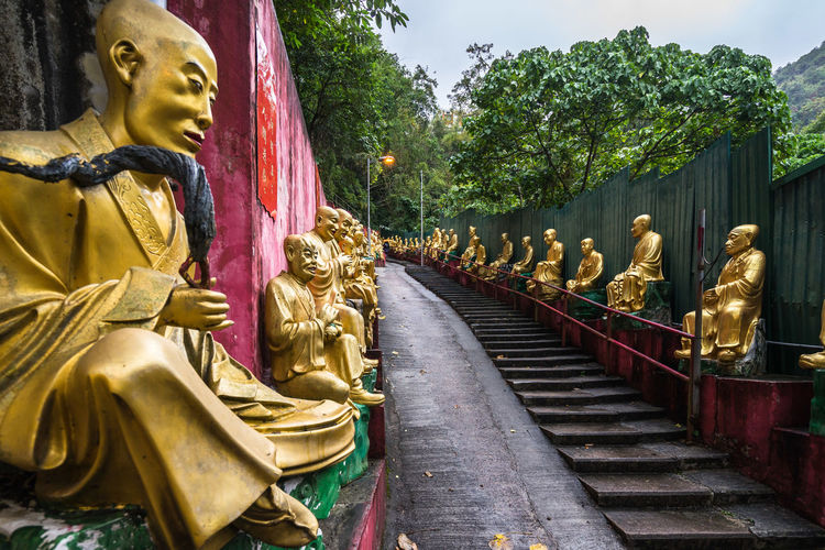 Steps amidst golden statues against trees
